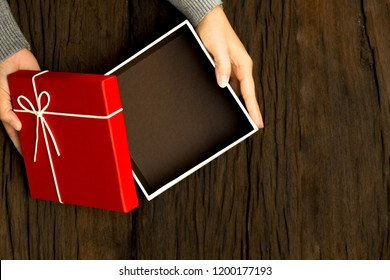 Top view of female hands holding red gift box on wooden background and and open the box with space to put products