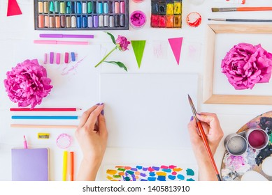 Top view Female Hands holding painting brush over blank canvas with paintiing materials and flowers on white wooden background. Add more colors to your life, be cheerful motivated inspired Concept
