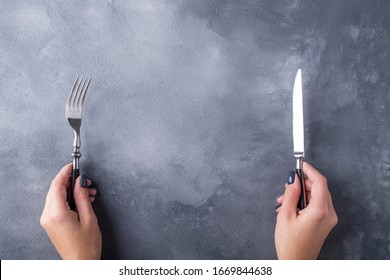 Top view of female hands holding fork and knife on gray background. Text space