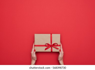Top view of female hands holding present box package in the palms isolated over flat lay background