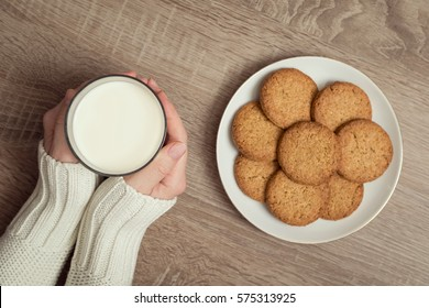 Top view of female hands holding a glass of milk, with plate of chocolate chip cookies placed next to it on the table. Selective focus