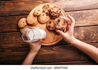 Top view of female hands holding a glass of milk, with plate of chocolate chip cookies placed next to it on the table. Selective focus. Cookies with milk and rustic wooden table.