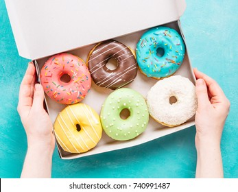 Top view of female hands holding box with colorful donuts on blue concrete background