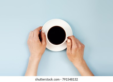 Top view of female hands holding espresso cup over blue background.