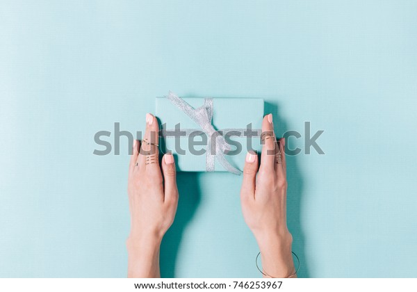 Top view of female hands holding box with gift and ribbon on blue background