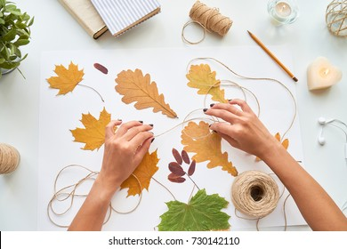 Top view of female hands making handmade autumn leaves decoration for interior