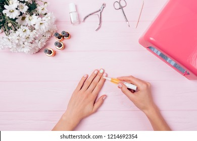 Top view female hands nourishing skin after gel manicure near UV lamp, tools and bouquet of flowers on pink table. Flat lay arrangement woman complete shellac procedure apply cuticle oil on nails.