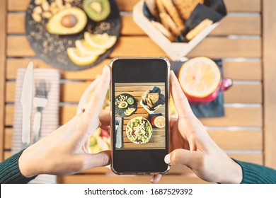 Top view female hands taking photo with mobile smartphone on health lunch food - Young girl having fun with new technology apps for social media - People healthy lifestyle and tech addicted concept