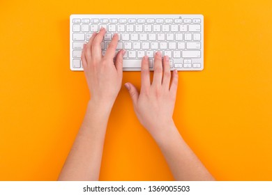 Top view of female hands using computer keyboard while working, orange background. Solution, business planning, financial analysis, start up. Business concept.