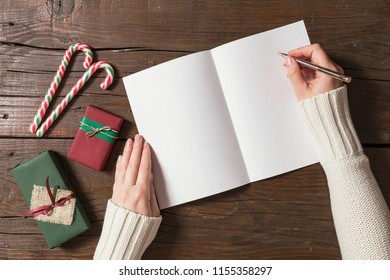 Top view of female hands writing a letter to Santa. Christmas presents and decorations placed on wooden table next to the letter