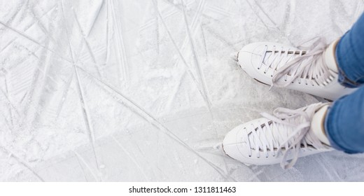top view of female legs in skates and copy space over white ice at rink