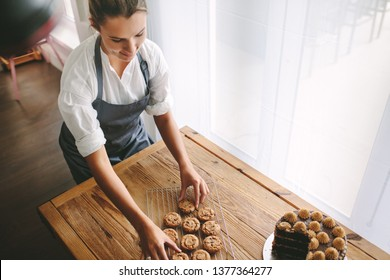 Top view of female pastry chef preparing cookies in the kitchen. Woman baker arranging cookies on grill with a cake on table.