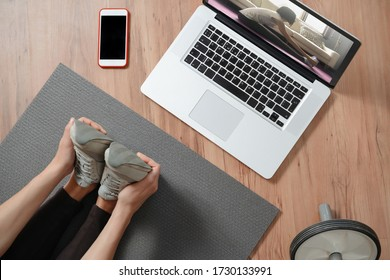 Top view of female stretching legs at home using laptop for online classes. Fitness exercises, healthy lifestyle. Online workout at home due to coronavirus outbreak and quarantine. Remote training