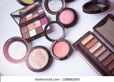Top view of female table with makeup eye palette, foundation and others.