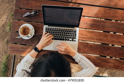 Top view of female using her laptop at a cafe. Overhead shot of young woman sitting at a table with a cup of coffee and mobile phone surfing the net on her laptop computer.