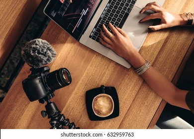 Top view of female vlogger editing video on laptop. Young woman working on computer with coffee and camera on table.