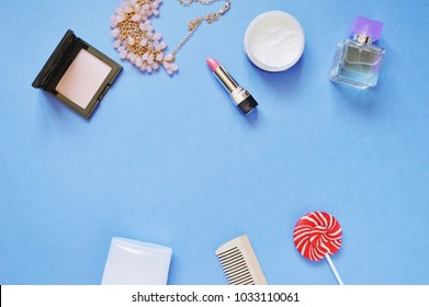 Top view feminine table. Compact powder, necklace, pink lipstick, face cream, perfume bottle, shampoo, wooden hair brush and red candy. Spring and summer beauty background. International Women's Day