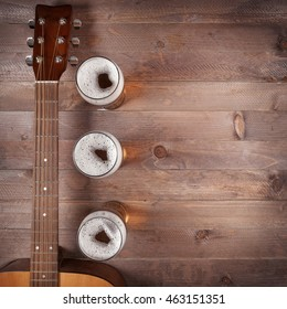 top view of few glasses of beer near neck acoustic guitar on wooden table. Blank space for text