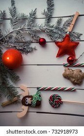 Top view of fir branches with christmas decoration, burning candle, candies on wooden background. Copy space for your text