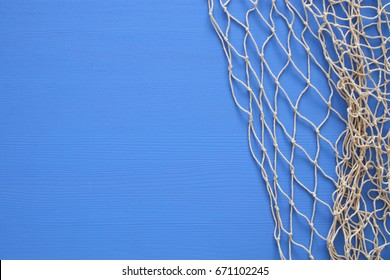 Top view of Fishnet on blue wooden background.