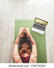 Vista superior para una mujer deportiva que se sienta en el tatami en la pose Paschimottanasana, haciendo ejercicios respiratorios, viendo clases de yoga en línea en el ordenador portátil. Gente sana y concepto de automotivación.