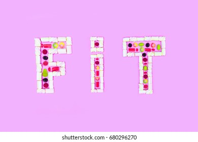 top view of fit word made of colorful sweets isolated on pink