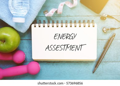 Top view of fitness equipment, healthy food, mobile phone and open notebook written with ENERGY ASSESMENT on wooden background.