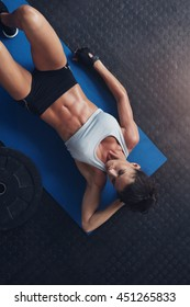 Top view of fitness woman relaxing after exercise session on floor. Young female lying on exercise mat in gym.