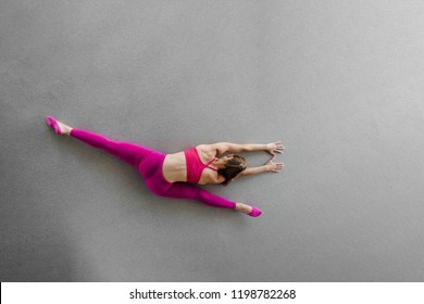 Top view of fitness woman at stretching training doing splits with copy space