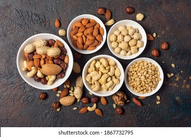 Top view of five bowls with almond, hazelnut, walnut, peanut, cashew and pine nuts on dark concrete background