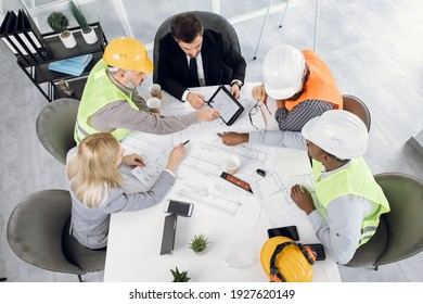 Top view of five diverse people in suits and helmets sitting at office with blueprints and gadgets. Qualified construction team planning arrangement of service lines of new building.