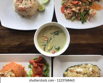 Top view of five type of Thai dishes served on a table. Seafood fried rice, seafood fried noodle, green curry soup, Tomyam fried rice and Thai seafood pineapple rice.