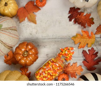 A top view, flat lay background image of halloween pumpkins and fall leaves on a rustic wood table. Add your text in the copyspace area.