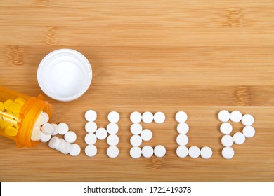 Top view flat lay bottle of pain pills spilled on wood table spelling the word HELP. Addiction and opioid epidemic theme imager with copy space.