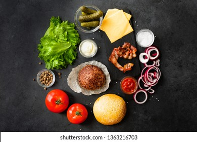 Top view and flat lay of burger ingredients and sauce on black table.