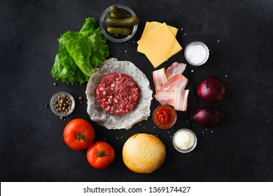 Top view and flat lay of burger ingredients and sauce on black table with copyspace. Burger food background
