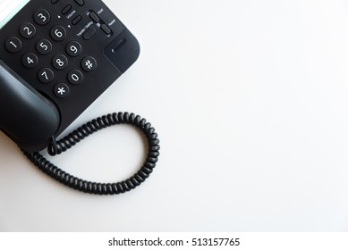 Top view or flat lay of digital voip black telephone on white desk, call center, contact center, customer service, customer support concept background with copy space, selective focus on dial pad