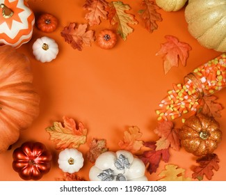 A top view flat lay fall halloween background image with orange pumpkins and leaves. Add your text to the copyspace.