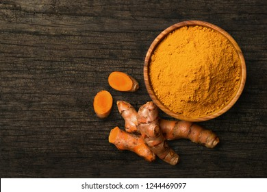 Top view (flat lay) of finely dry Turmeric (Curcuma longa Linn) powder in wooden bowl with rhizome (root) sliced on old wood background.