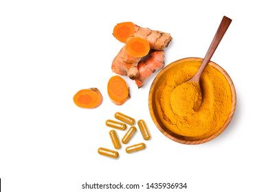 Top view (flat lay)  of finely dry Turmeric (Curcuma longa Linn) powder in wooden bowl with  rhizome (root) sliced and capsules isolated on white background.