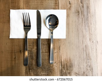top view flat lay fork, knife and soup spoon on the napkin on the table