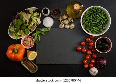 Top view, flat lay.  French cuisine. Ingredients for making French traditional niçoise (nicoise) salad around a black stone cutting board. Vegetables, quail eggs, anchovies. Copy space.