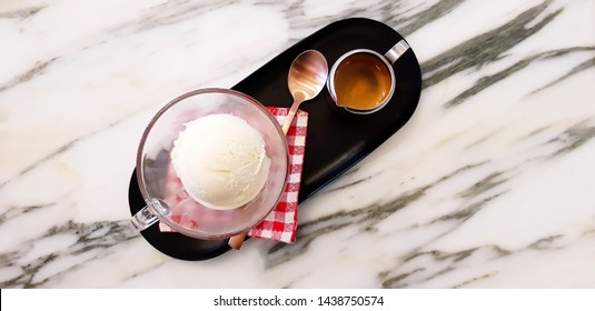Top view or Flat lay of glass of vanilla ice cream with stainless mug espresso mug shot, copper tea spoon and red plaid cotton in black tray on white marble table with copy space - Affogato coffee