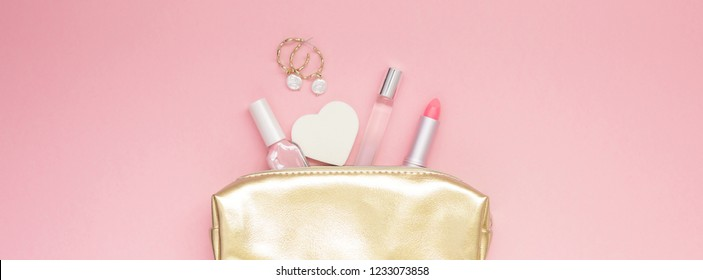 Top view flat lay of golden female purse with cosmetics earrings with copy space millennial pink color paper background minimal style. Template for feminine blog social media Long wide banner