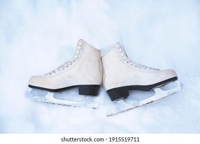 Top View, flat lay. Old, vintage white figure skates on white snow