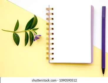 Top view flat lay picture with notepad as mockup for your design and different accessories on white and yellow background.