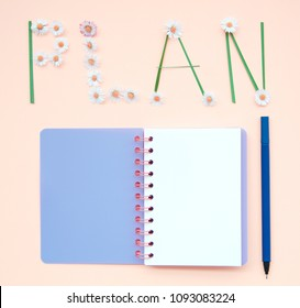 Top view flat lay picture with notepad as mockup for your design with flowers on pink background.
