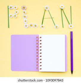 Top view flat lay picture with notepad as mockup for your design with flowers on yellow background.