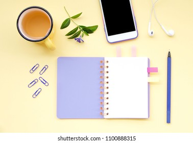 Top view flat lay picture with notepad as mockup for your design and different accessories on yellow background.