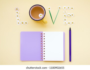 Top view flat lay picture with notepad as mockup for your design and different accessories on yellow background. Love message.